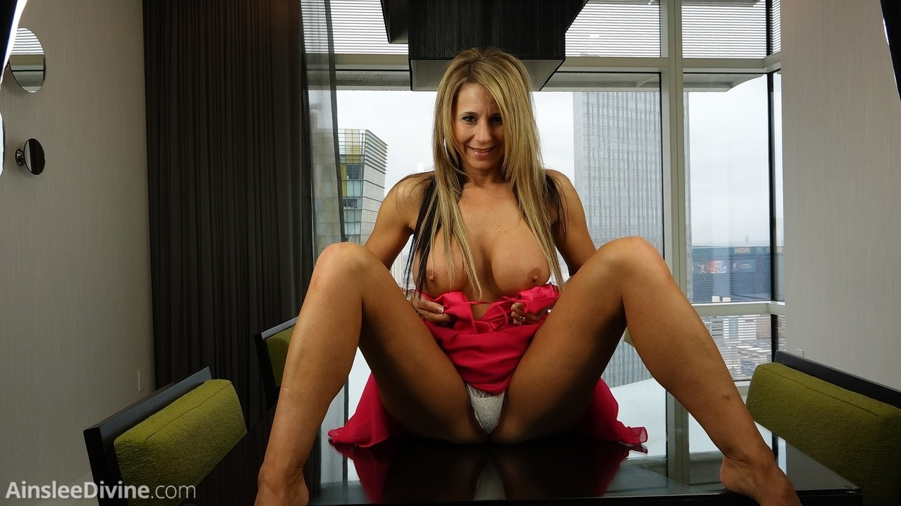 Big titted blonde Ainslee Divine gets naked on top of the dining table