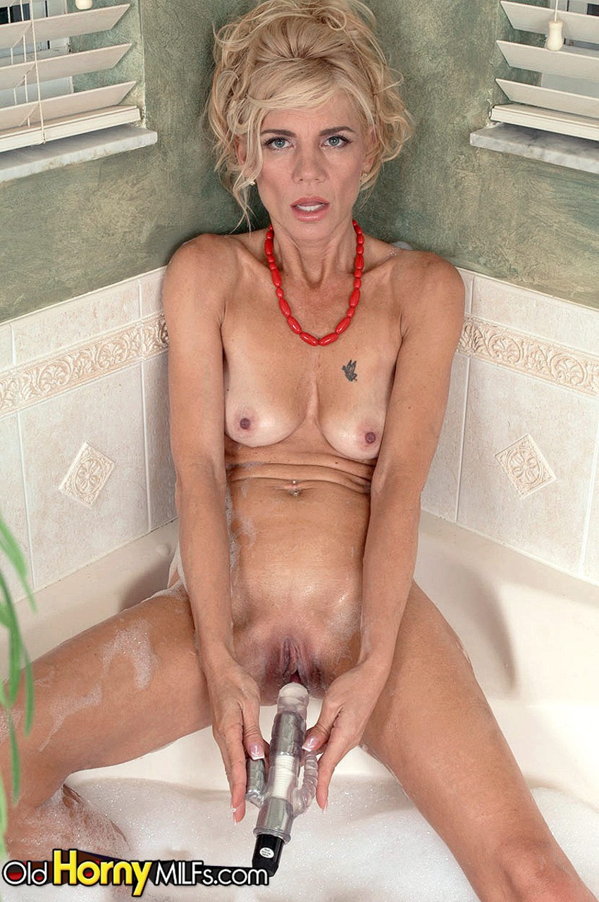Sexy mature woman Barbie Page masturbates in the tub after disrobing