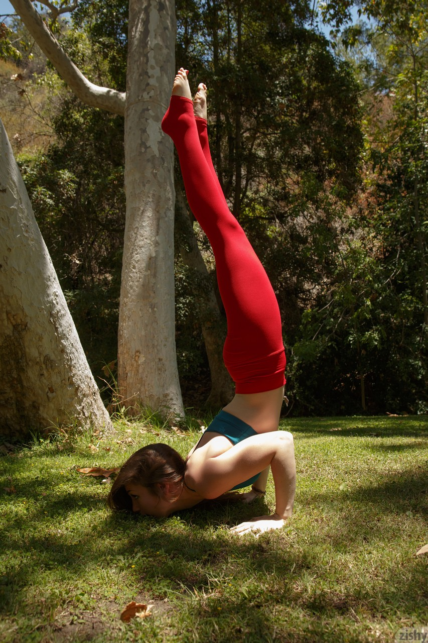 Clothed teen girl Diana Mackie works on her yoga moves in red leggings