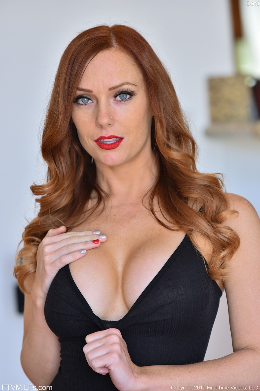 Middle-aged redhead frees her big boobs from her black onesie in heels