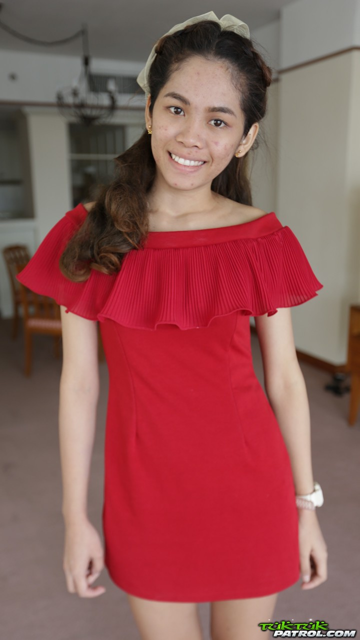 Cute first timer from Thailand poses in her red dress prior to modeling gig