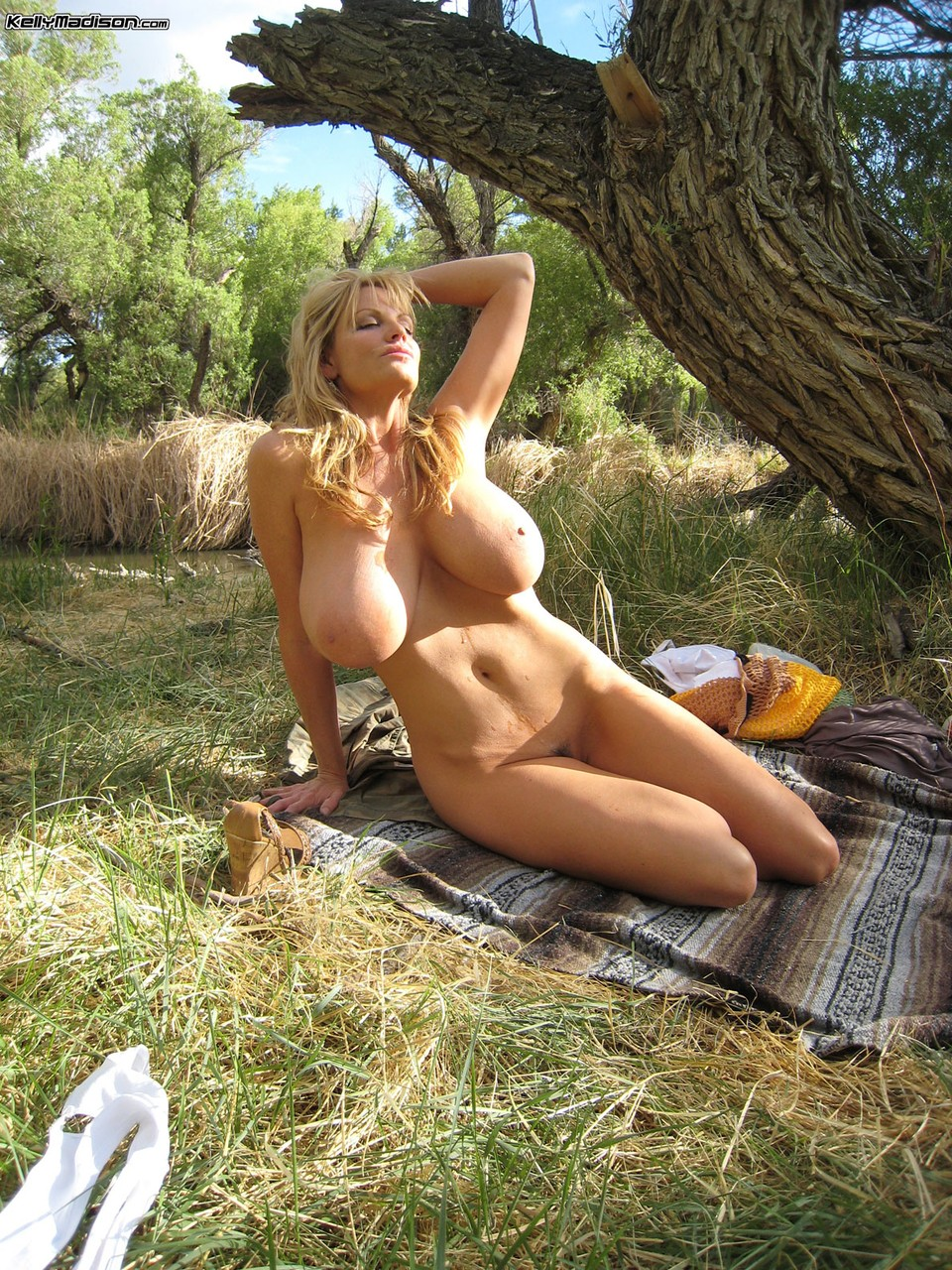 Stunning MILF with fantastic breasts Kelly Madison stripping by the river