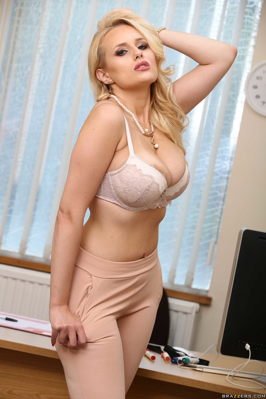 Blonde chick whips out her hooters while stripping naked in her office