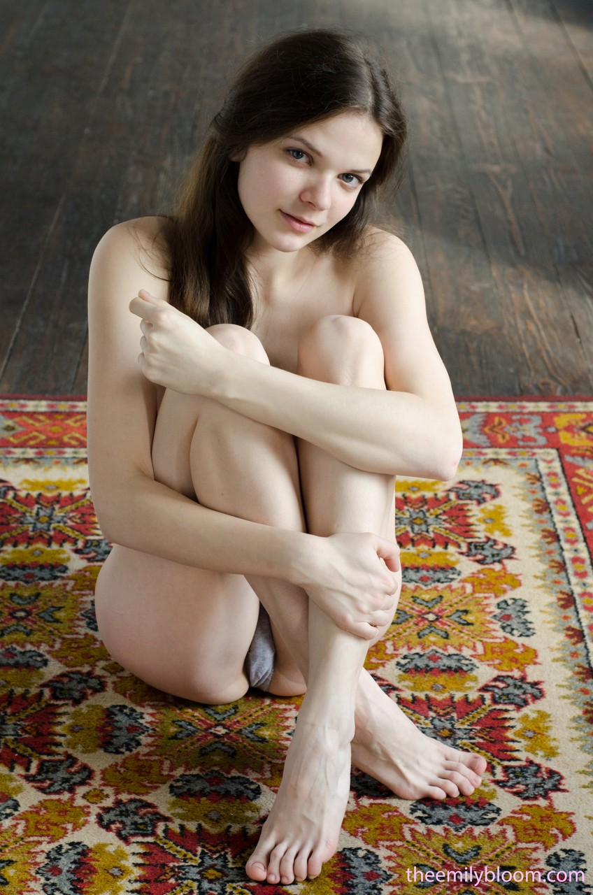 Horny brunete Emily Bloom gets completely naked and lays on the carpet