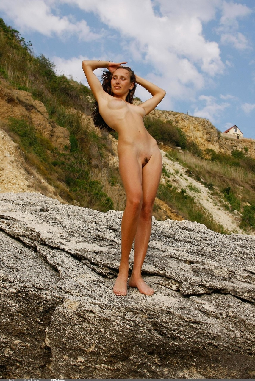 Slender solo girl poses her nude body high up on a rocky mountain