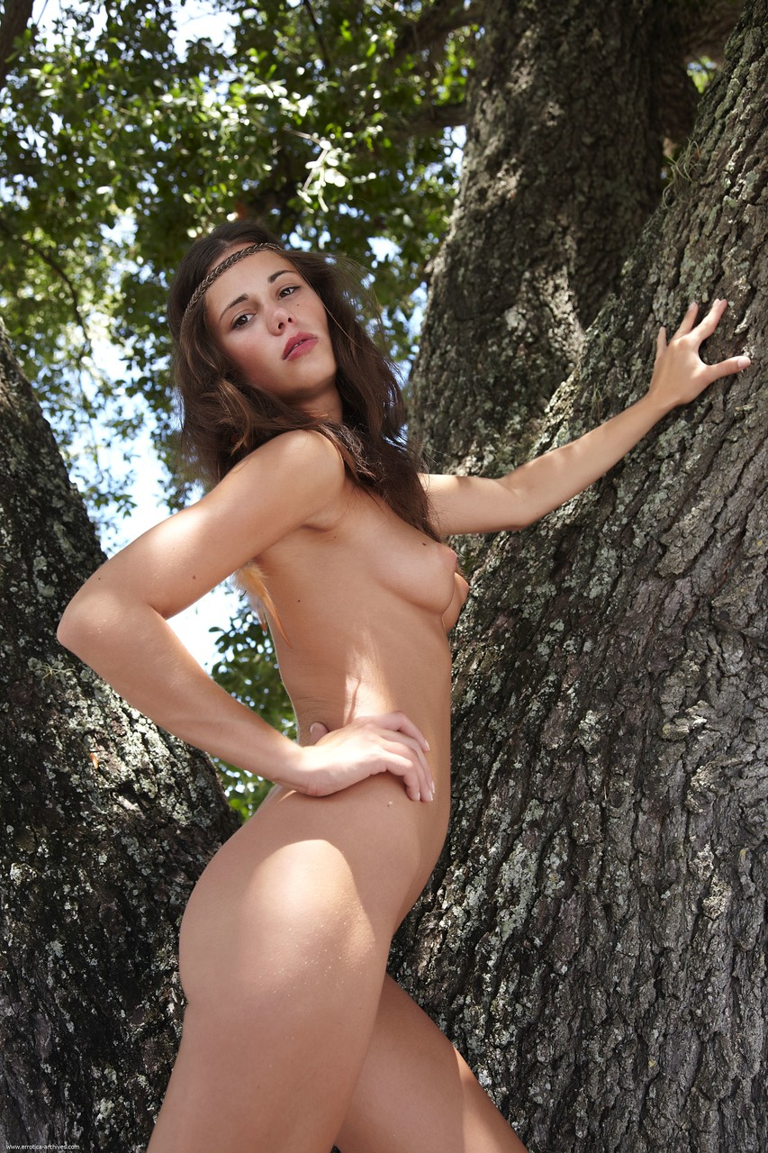 Barefoot female climbs a tree to model her hot body in the nude