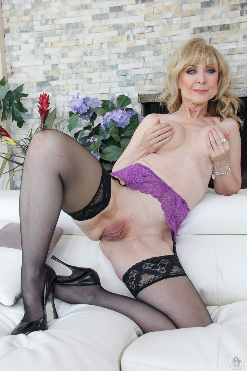 Hot MILF Nina Hartley posing on the bed all naked touching her big tits