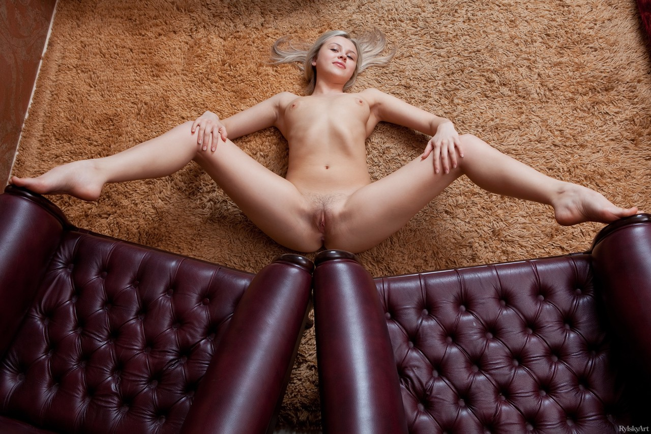Solo girl with a cute face poses her naked body on carpeted flooring