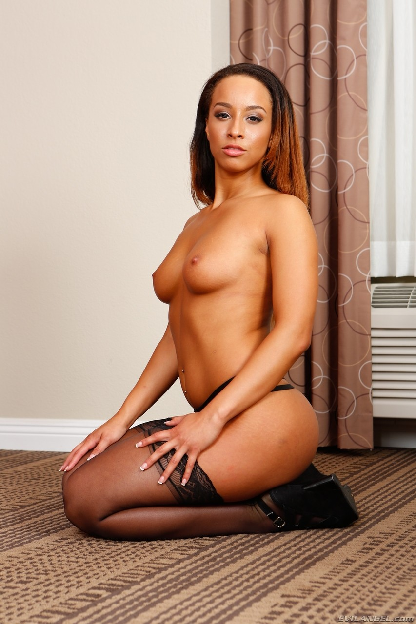 Ebony female frees her sexy ass from miniskirt in black stockings