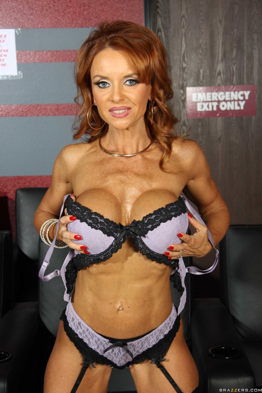 Mature redhead Janet Mason in fishnets proudly reveals her enhanced big tits