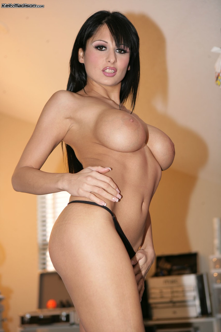 Brazen black haired slut flaunts her huge round breasts fully clothed  naked