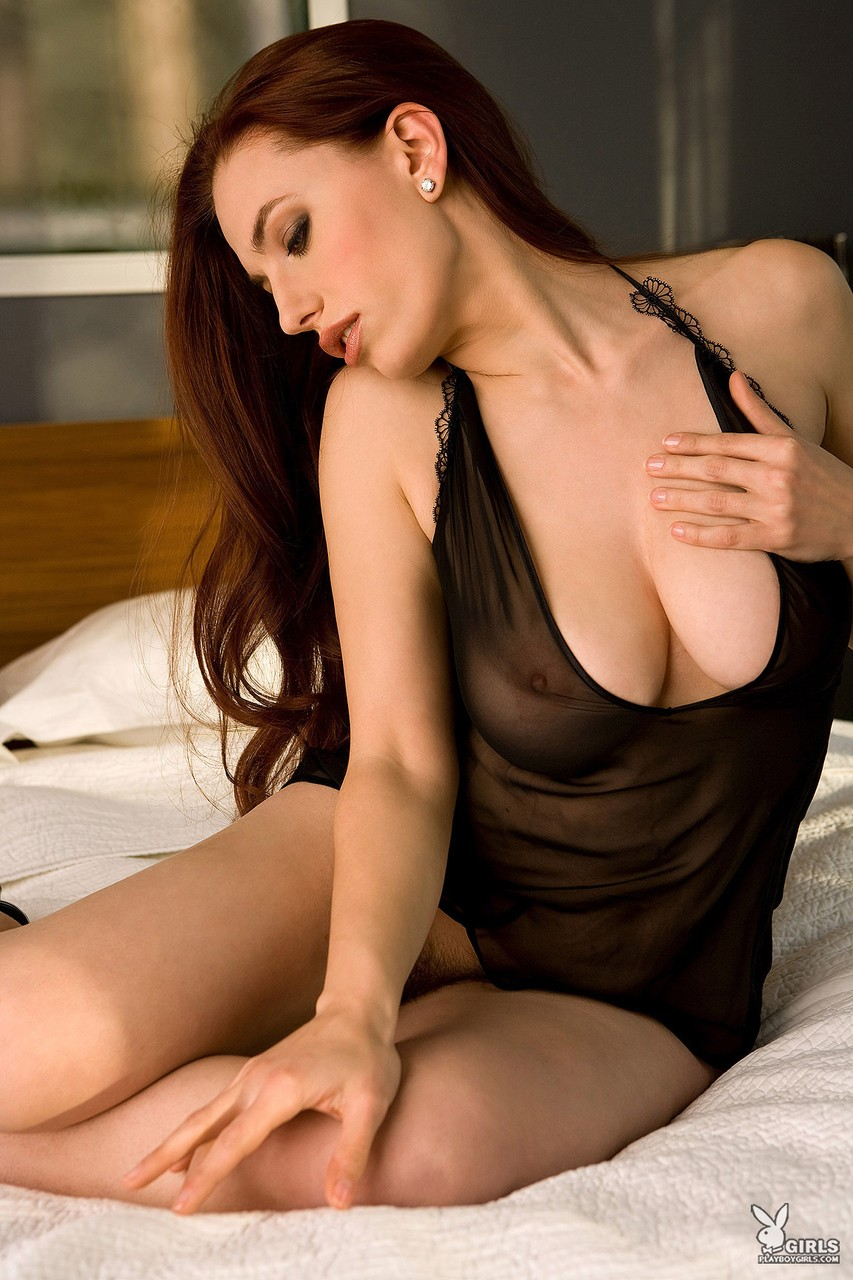 Seductive redhead Titania Lyn strips and rubs her pussy and tits gently