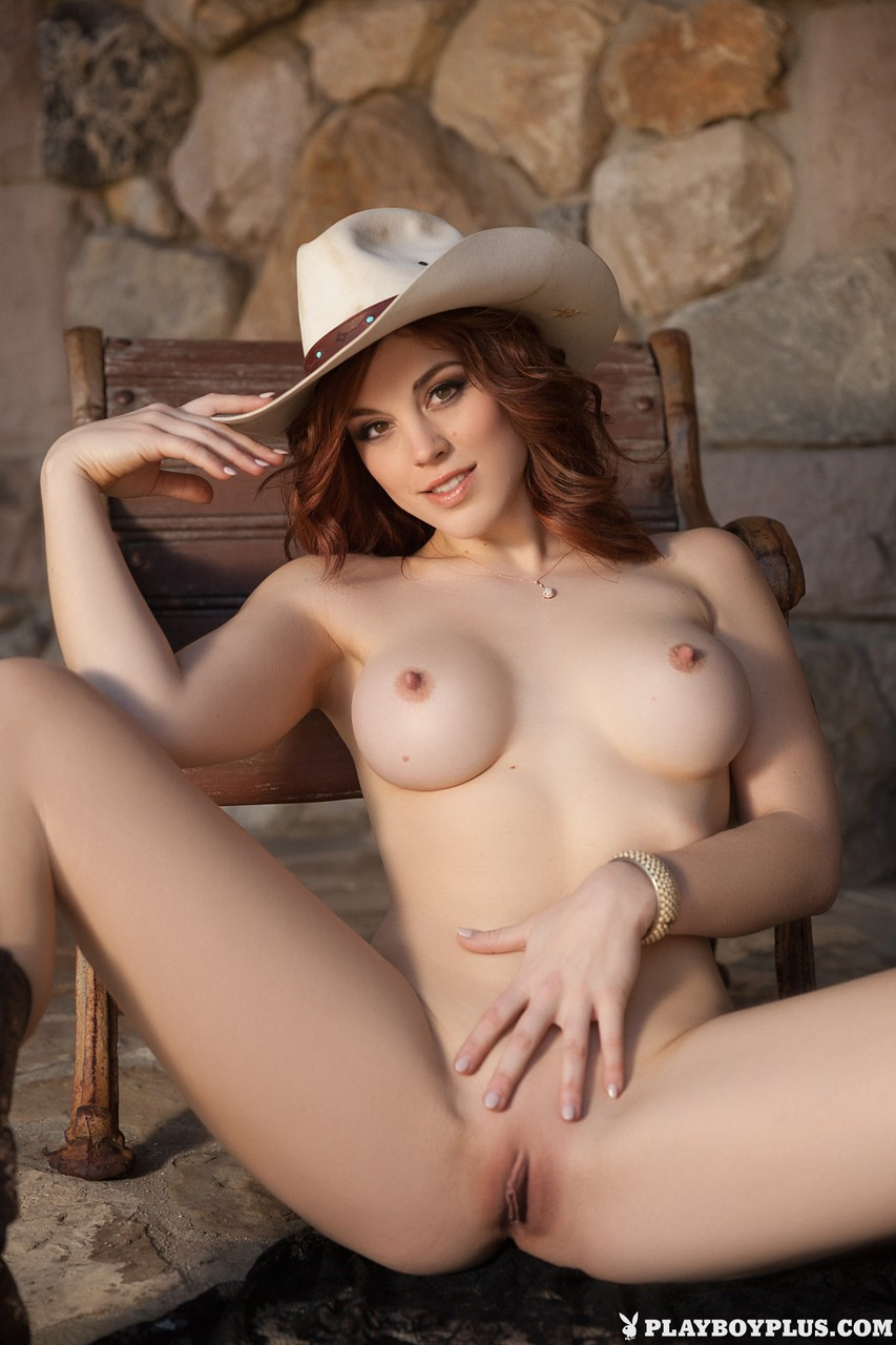 Brunette cowgirl Molly Stewart showing her fake tits and smooth pussy outdoors