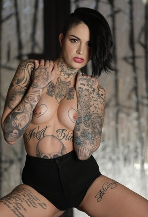 Tattooed alt model Leigh Raven peels off her bra and shorts to pose nude