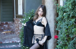 White girl Riley Reid models outdoors in black lingerie with matching hosiery