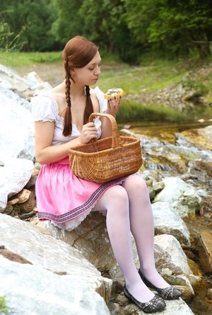 Young redhead pulls down her white hosiery and toys herself by a river
