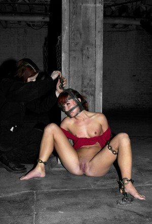 Naked redhead has her nipples and clit affixed with clamps while restrained