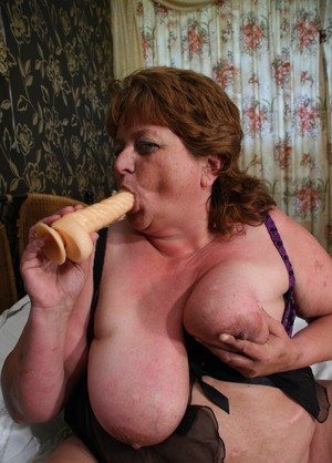 Obese old woman sucks on a dildo while spreading her pussy lips