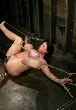 Restrained female Daphne Rosen is flogged prior to being machine fucked