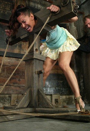 Isis Love finds herself being humiliated in the stocks with a hook in her anus