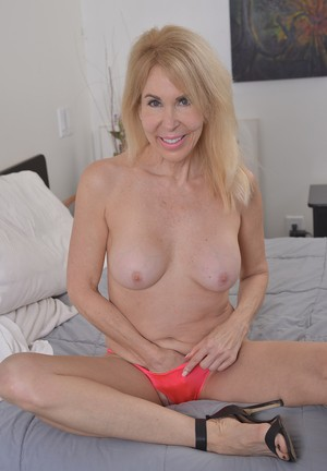 Aged blond lady Erica Lauren gets naked and pets her twat with her legs spread