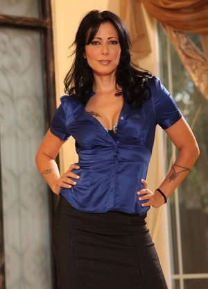 Middle-aged brunette Zoey Holloway strips to her black stockings
