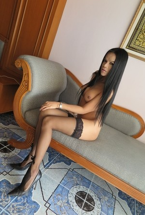 Shemale Aimee wears high heels and stockings while stroking her big cock