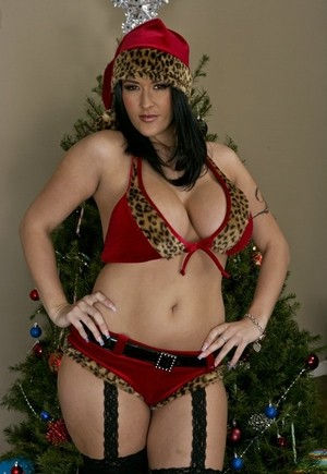 Dark haired MILF Carmella Bing unleashes her knockers afore the Christmas tree