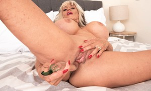 Petite granny Sally D'Angelo enjoys showing off her big fake tits