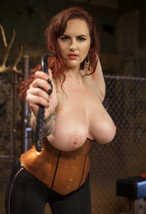 Redhead female Mz Berlin unleashes her knockers with a whip in her hand