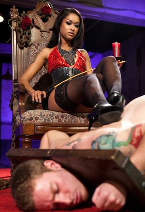 Petite but very strict queen Skin Diamond dominates over man in wooden stocks