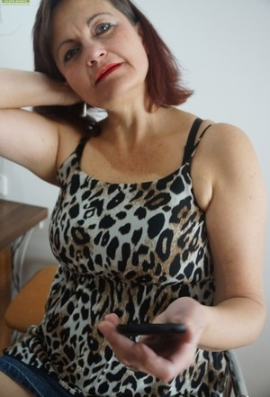 Mature redhead Justina Sindell strips and touches her fat hairy snatch