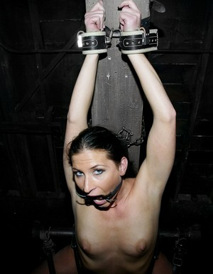 Brunette slave was chained to a column and punished with pins and sex machine