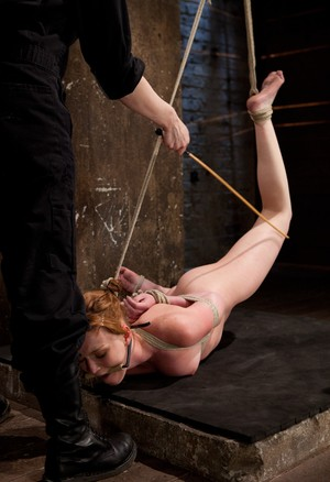 Redhead female Marie McCray us caned during bondage session with a woman