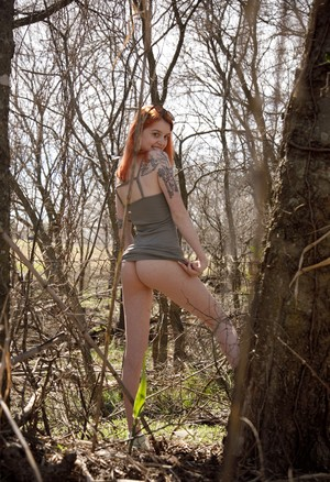 Redhead babe Wanda Ablee likes to show her big tits in the forest