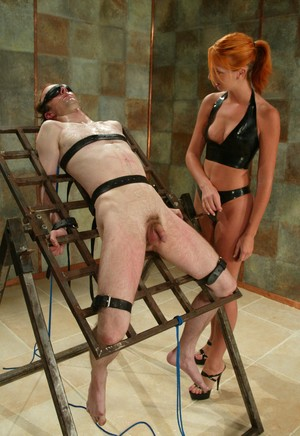 Redhead dominatrix humiliates a helpless male slave on a homemade rack
