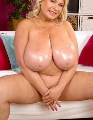 Obese blonde female applies oil / lotion to her massive breasts