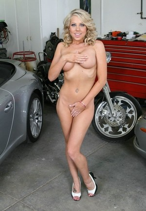 Naked blonde chick covers up her private parts with her hands in a garage
