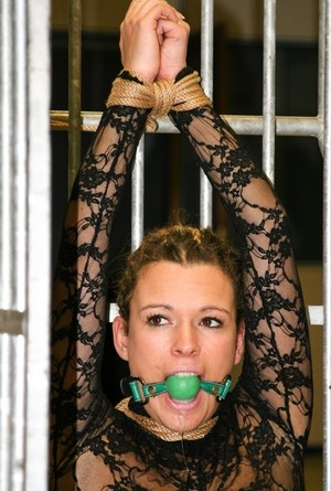 Gagged Vixen gets tied up with rope while she is in a half-open cage