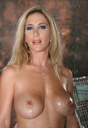 Lovely MILF Savannah Jane sits on the chair and shows her sexy ass & tits