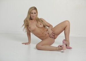 Sexy blonde MILF uncovers her big boobs as she strips to high heels only