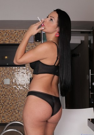 Dark haired shemale Bruna Castro models black lingerie while smoking
