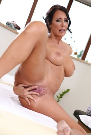 Middle-aged brunette woman Reagan Foxx reveals her large boobs as she strips