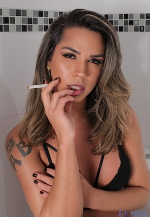 Leggy shemale Amanda Fialho smokes a cigarette in her lingerie atop the toilet
