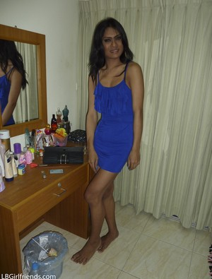 Dark-skinned ladyboy in blue dress flashes black panties solo in bedroom