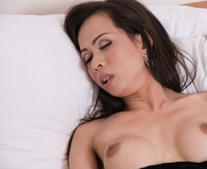 Lonely shemale from Asia relaxes on bed and keeps jerking small dick