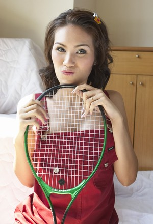Shemale tennis player from Asia never puts aside her racket even posing naked