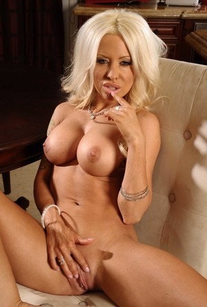 Blond chick Helly Mae Hellfire uncovers her big tits as she strips naked