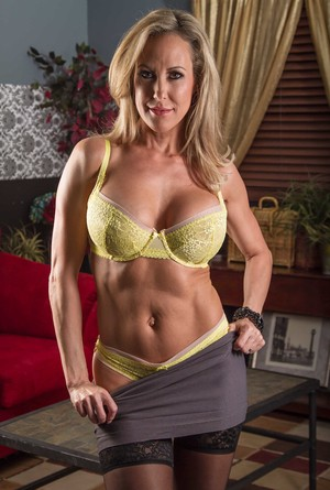 Solo model Brandi Love uncovers her big tits as she strips off her clothes