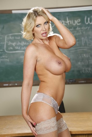 Blonde schoolteacher Leigh Darby bares her big tits as she strips at her desk